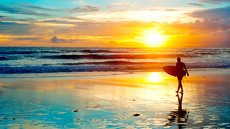 Surfer-on-the-ocean-beach-at-sunset-on-Bali-island.jpg