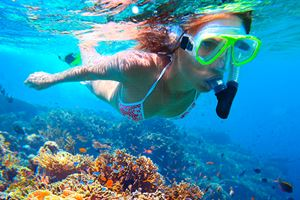 Woman-with-mask-snorkeling-in-clear-water-over-vivid-coral-reef.jpg
