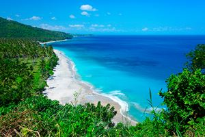 Tropical-lagoon-with-clear-water-and-beach-with-white-sand-and-palm-trees-in-a-valley.jpg