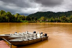 Small-motor-boats-tied-up-at-a-small-dock-on-a-chocolate-brown-colored-rain-forest-river.jpg
