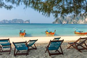 Bamboo-beach-chairs-and-traditional-long-tail-boats-on-beautiful-bay-of-Koh-Phi-Phi-Island.jpg