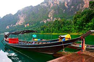 Longtail-boat-is-parking-in-front-of-raft-house-in-Chiew-Lan-Lake.jpg