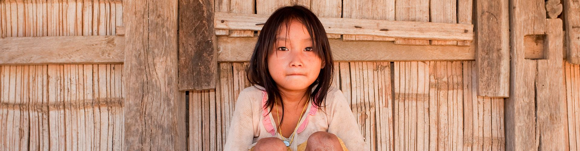 Asian-girl-Akha-before-timber-house,-Laos.jpg